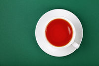 White cup of black tea on saucer over green