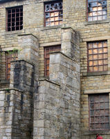 a large decaying old abandoned factory building with boarded up and broken windows