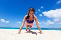 Woman doing push ups on beach