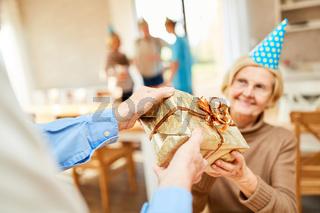 Senior Frau wird mit einem Geschenk überrascht