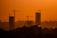Industrial Construction Cranes and Building Silhouettes at Sunset
