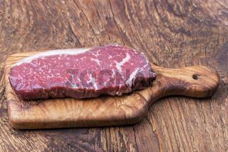 rohes Steak auf Olivenholz