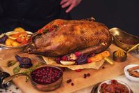 Roasted goose with herbs berries and vegetables