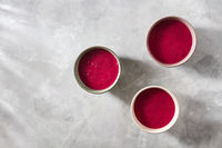 Three bowls with red beet smoothies on a concrete background, flat lay
