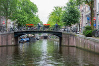 Amsterdam Canal with view at bridge with bicycles and people