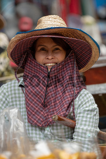 Smiling woman in floating market looks up