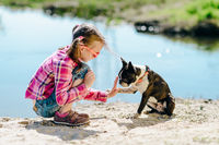 Child girl playing with boston terrier dog on the sandy river bank outdoors