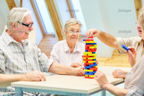 Senioren bauen einen Turm aus Bausteinen