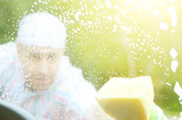 Man in green gloves washing car window with yellow sponge