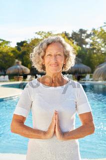 Senior Frau macht Yoga Meditation am Pool