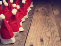 Many hats of Santa on a rustic wooden table