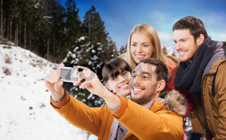 happy friends with camera over winter background