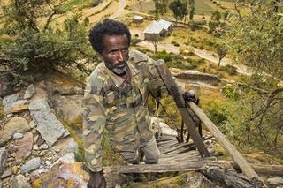 Einheimischer Mann auf der Holzleiter zur  Felsenkirche Petros and Paulos Melehayzengi, Äthiopien