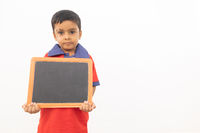 Concept of child protest showing with young boy holding black slate on isolated background.