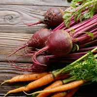 Fresh organic beetroots and carrots on kitchen wooden rustic table close up view