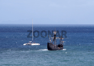 he replica santa maria sailing ship leaving funchal in madeira with a catamaran on a coastal tourist trip