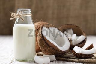Glass bottle of milk or yogurt on hemp napkin on white wooden table with coconut aside
