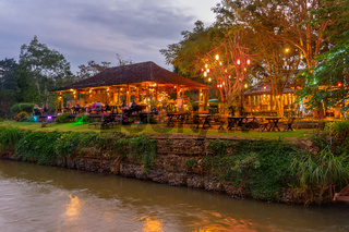 Illuminated outdoor restaurant by river