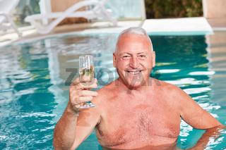 Senior Mann im Pool mit einem Sektglas