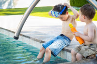 Young Mixed Race Chinese and Caucasian Brothers Wearing Swimming Goggles Playing At The Pool