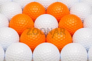 White and orange golf balls in the box