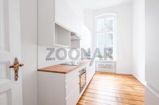 empty, new  built-in kitchen with white furniture and wooden floor