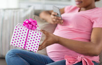 african pregnant woman with smartphone and gift
