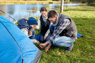happy parents and son setting up tent at campsite