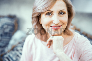 Beautiful mature woman gently smiles at camera