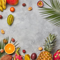 Bright composition of different exotic fruits and palm green leaves on a gray concrete background with copy space. Food background. Flat lay