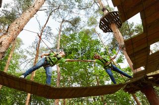 Zwei Kletterer helfen sich im Hochseilgarten