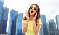 amazed teenage girl in sunglasses at singapore