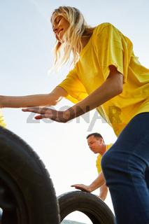 Junge Frau rollt einen Autoreifen beim Wettkampf