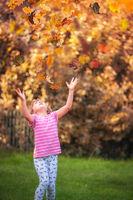 Girl catching leaves in autumn