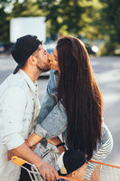 Young, loving parents kiss in the parking near the supermarket.