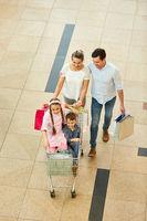Familie und zwei Kinder mit Einkaufswagen