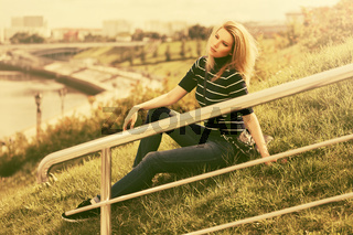 Young fashion woman in striped turtleneck t-shirt sitting on the grass outdoor