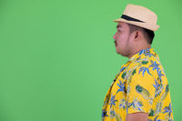 Profile view of young overweight Asian tourist man