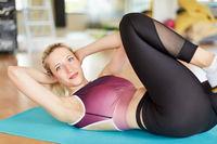 Frau macht seitliche Crunches im Fitnesscenter