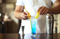 Barman at work, preparing cocktails. Pouring blue lagoon cocktail glass