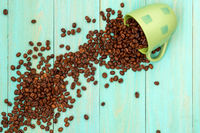 Cup with scattered coffee beans