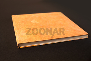 Closed blank notebook isolated on black