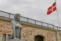 Mermaid statue and danish flag close to the main harbour of Copenhagen