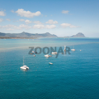 Top down aerial view of boats on the reef of tropical beach of Black River, Mauritius island