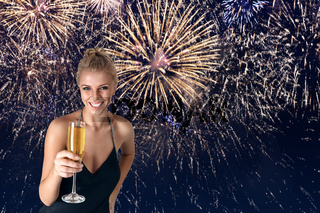 Young woman celebrating party with glass of champagne in her hands in front of fireworks