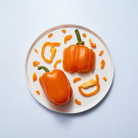 yellow peppers slice and half on white plate isolated on gray