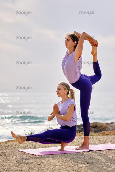 Women practising yoga do Natarajasana Lord of the Dance Pose outdoors