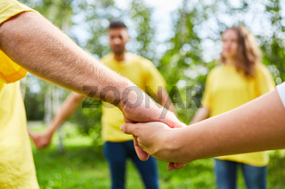 Gruppe hält sich an den Händen beim Teambuilding