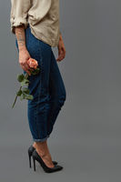 Elegant fashionable girl in jeans, black high-heeled shoes and with a tattoo is holding a fresh rose flower around a dark background with copy space for text.