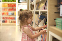 Little cute child picking books from the bookshelf